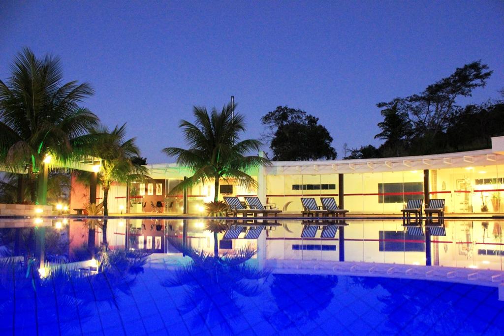 Piscina-do-hotel-com-coqueiros-iluminados-ao -fundo